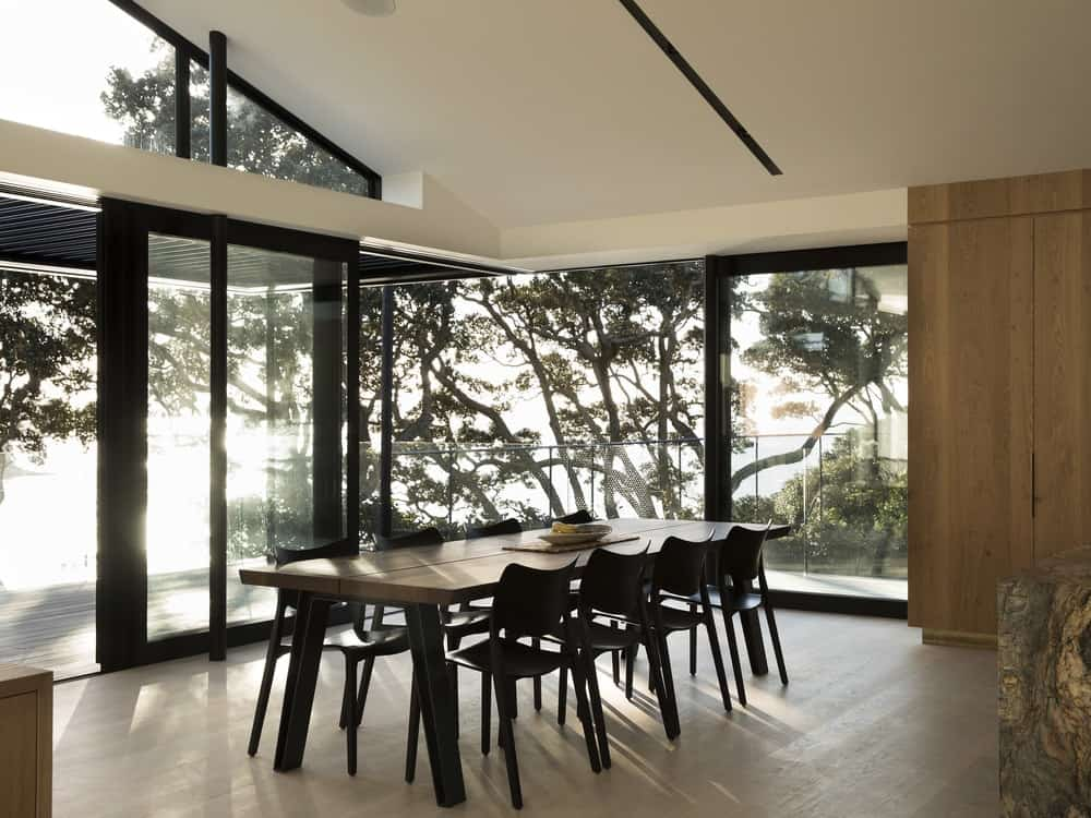 This is a modern dining room that has a large rectangular dark dining set that contrasts with the tall white cathedral ceiling brightened by the surrounding glass walls.