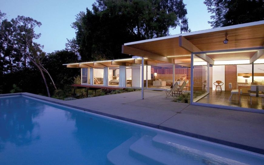 Paseo Miramar is a hillside mid-century modern home that was expanded with a pool and deck jutting out from the structure surrounded by shrubbery and greenery and with panoramic views.