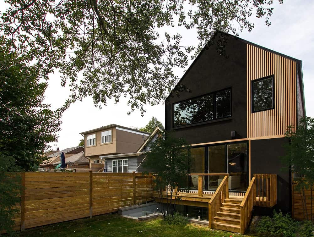 This is a close look at the back of the house that has unique combinations of black exterior walls and wooden shiplap walls to its exterior along with large glass windows and walls that look out onto the backyard that has a grass lawn.