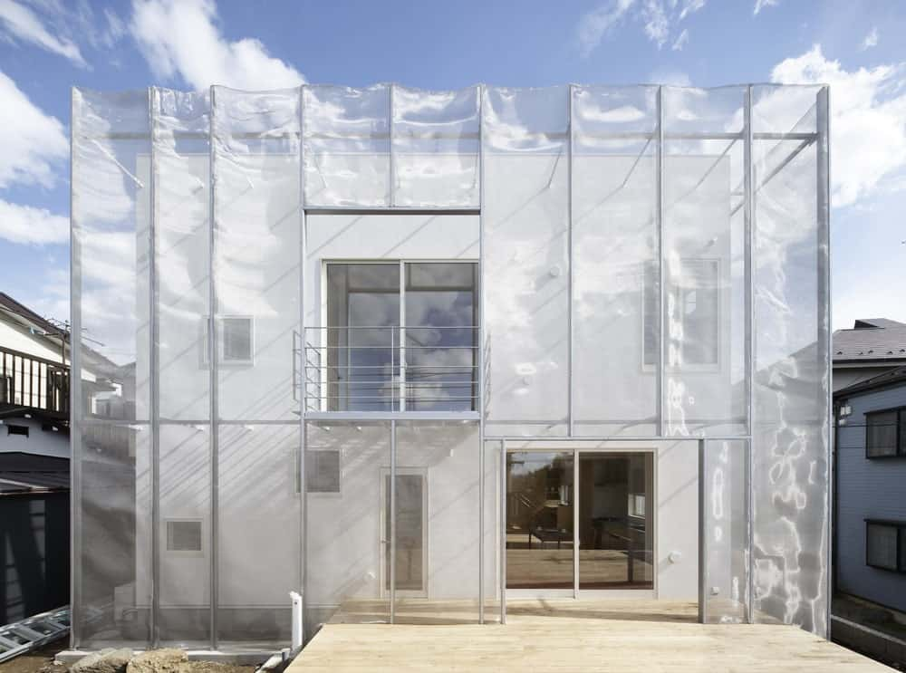 This is a front view of the Contemporary-style home with a walkway leading to the main entrance of the house with bright white exterior walls. These are then complemented by the opaque net outer cover of the exterior that gives it a unique look.