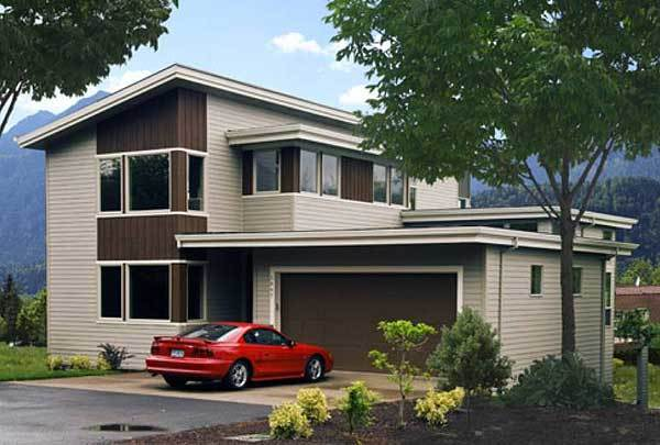This is a front view of the house exterior with a wide driveway and dark wooden exterior panels thata re complemented by the tall trees and shrubs of the front lawn landscaping.