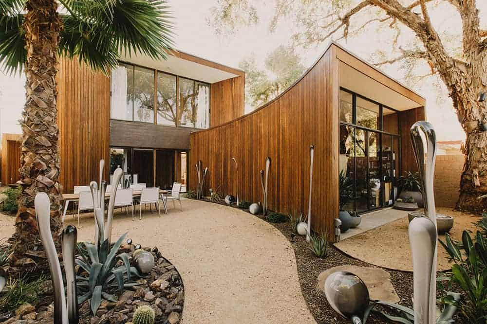 This is a close look at the back of the house that has wood-paneled exterior walls and a large curved structure on the side with glass walls. This also shows the outdoor dining area and the landscaping with unique art pieces.