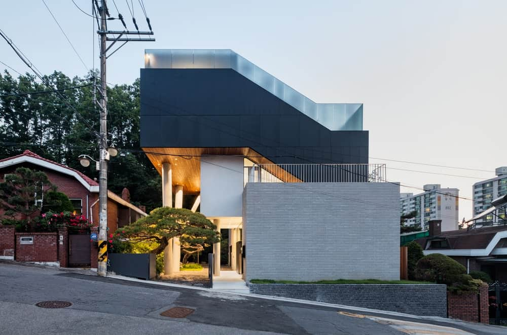 This is a front street view of the house that follows the lay of the land and has a unique and Contemporary design with large modern structures and tall pillars that support them. These are then complemented by the landscaping and the warm lighting.