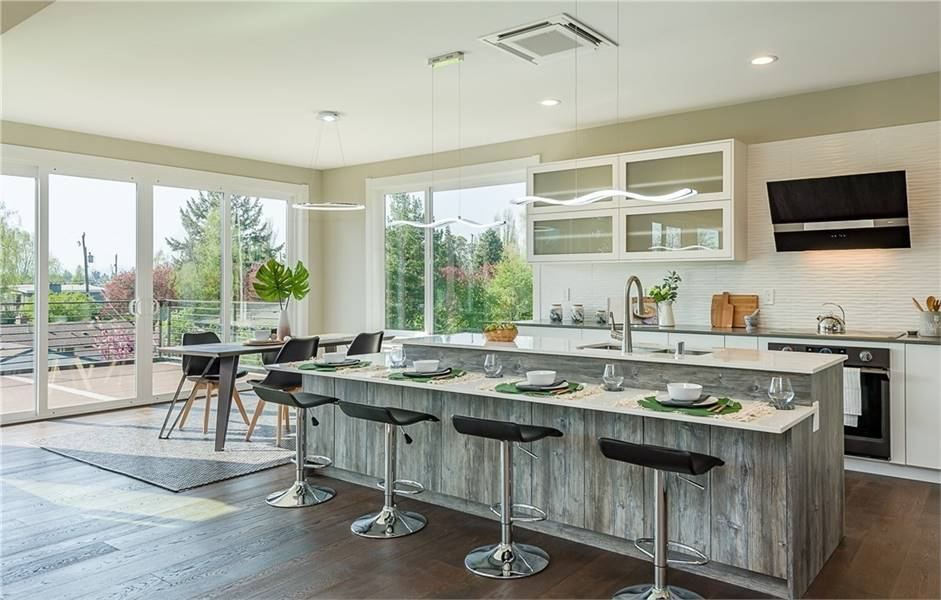 Bright and airy kitchen with sleek white cabinets contrasted by a rustic two-tier island. It has large windows and doors that provide a wonderful view of the surrounding.
