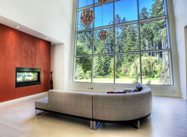 This is a spacious and airy living room with a large curved gray sectional sofa, a massive glass wall and a modern fireplace houses in an earthy red wall.