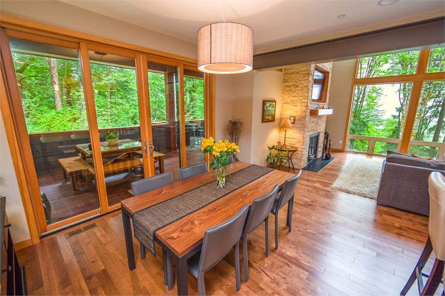 An open dining area with a modern drum pendant light, brown chairs, and a wooden dining table that blends in with the hardwood flooring.