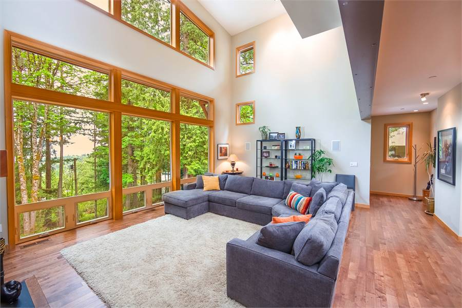 Bright living room with L-shaped sectional, a shaggy area rug, and metal shelving units placed against the beige walls. Massive windows take in magnificent views and an abundant amount of natural light.