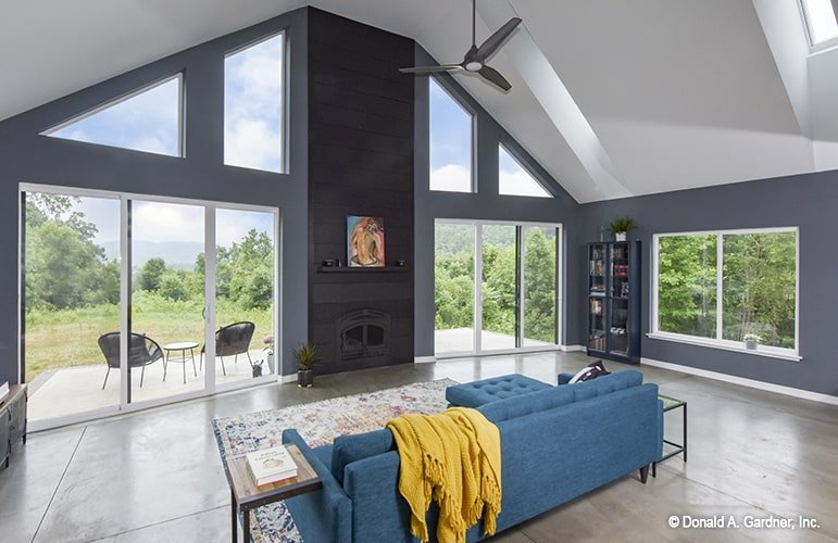 Sleek windows and glass sliding doors surround this modern living room. It includes a fireplace and a blue tufted sectional that adds a pop of color to the room.