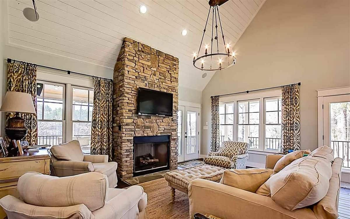 The earthy brown stone panel that houses the modern fireplace and the TV above it stands out against the bright beige walls and tall arched ceiling that hangs a round chandelier over the set of cushioned sofa and arm chairs.