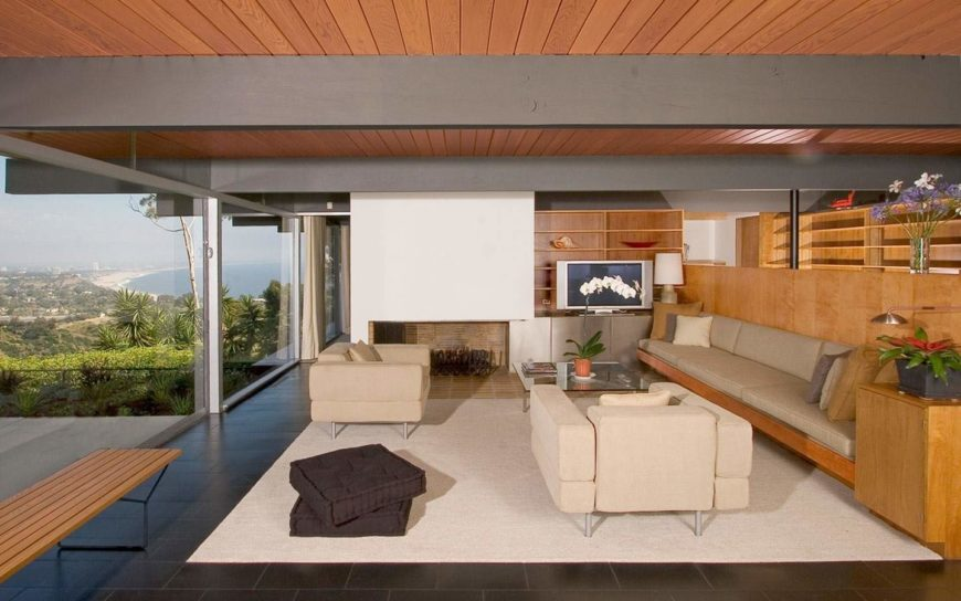 The living room has floor to ceiling windows overlooking the lush landscape. It features sparse lines and a streamlined natural look with beam ceiling and a neutral color scheme.
