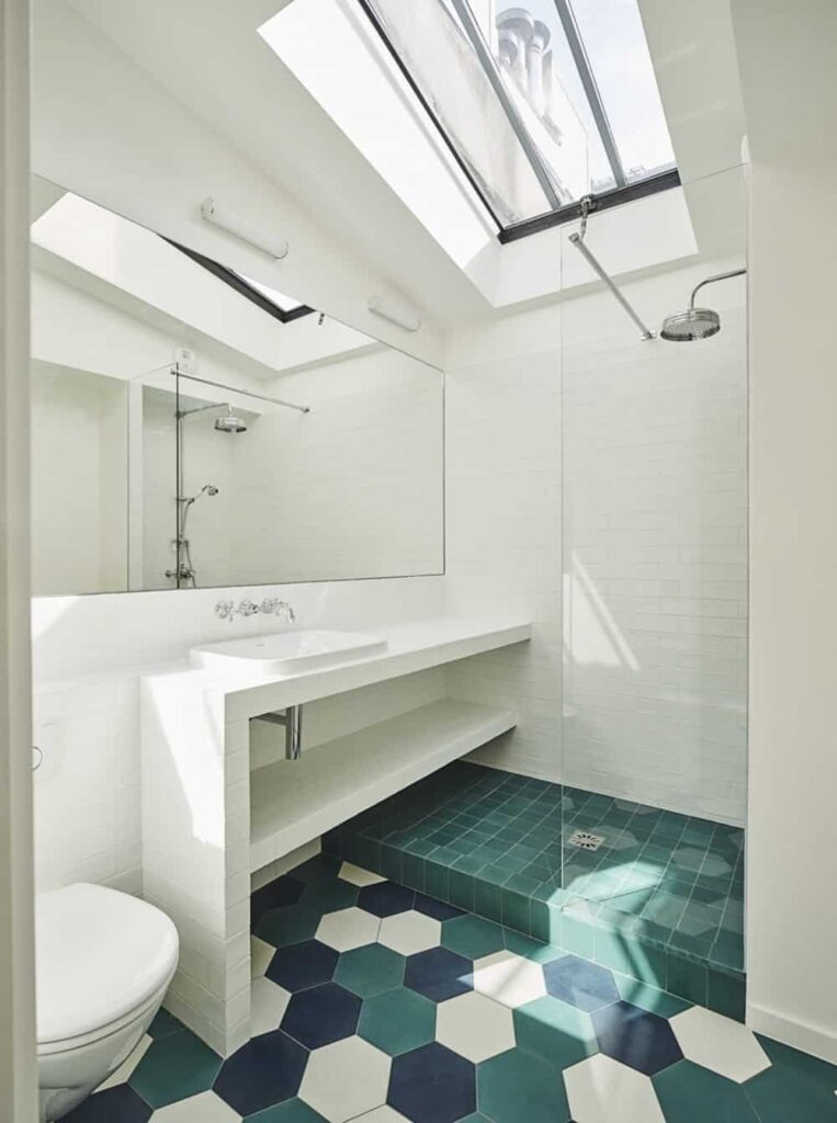 Natural light passes through the skylight in this white primary bathroom. It includes green tiles flooring and an open shower area.