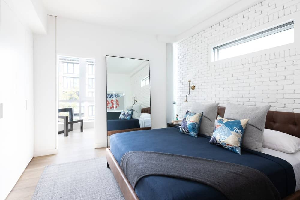 This is the other bedroom with a white brick wall behind the cushioned headboard of the bed that has blue sheets and various pillows. This is then adorned with a large leaning mirror on the side.
