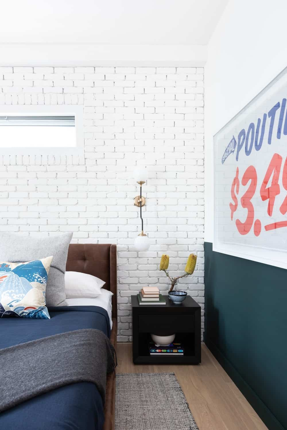 This is a closer look at the lovely white brick wall behind the dark brown cushioned headboard of the bed paired with a small black bedside table. These are then adorned with a vintage signage mounted on the wall beside the bed.