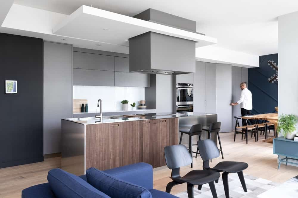 This is the beautiful kitchen beside the living room. Here you can see the kitchen island with a modern waterfall design and a dark brown tone that makes it stand out against the light hardwood flooring.