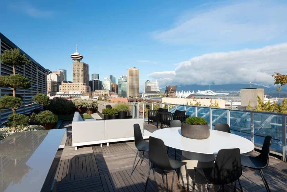 This is the rooftop patio that has an outdoor dining area. There is also a large L-shaped sectional sofa on the side adorned with multiple potted plants to augment the beautiful sweeping view of the city skyline.