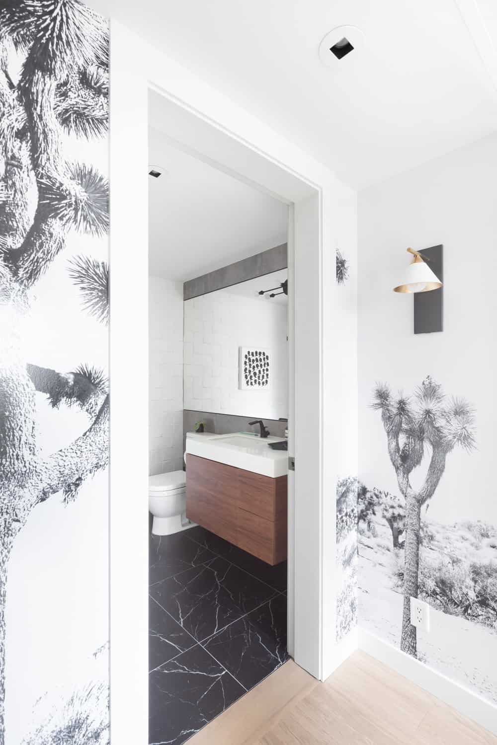 The hallway with the desert landscape wallpaper leads to a bathroom with a floating dark wooden vanity paired with a black flooring.