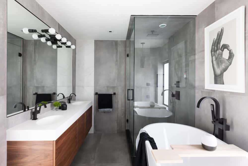 This is the primary bathroom with a white freestanding bathtub contrasted by black fixtures and the dark gray walls that match the flooring. Next to the bathtub is the glass-enclosed shower area with the same black fixtures.