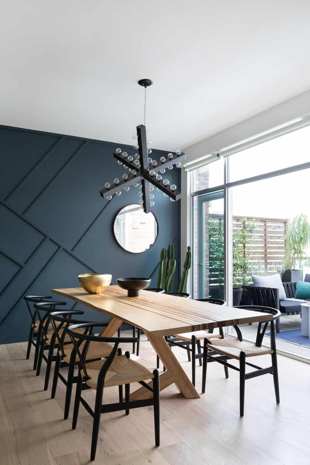 This is the charming dining area that has a large rectangular wooden dining table paired with black wishbone chairs that match well with the modern black decorative lighting and the navy blue textured and patterned wall on the far side.