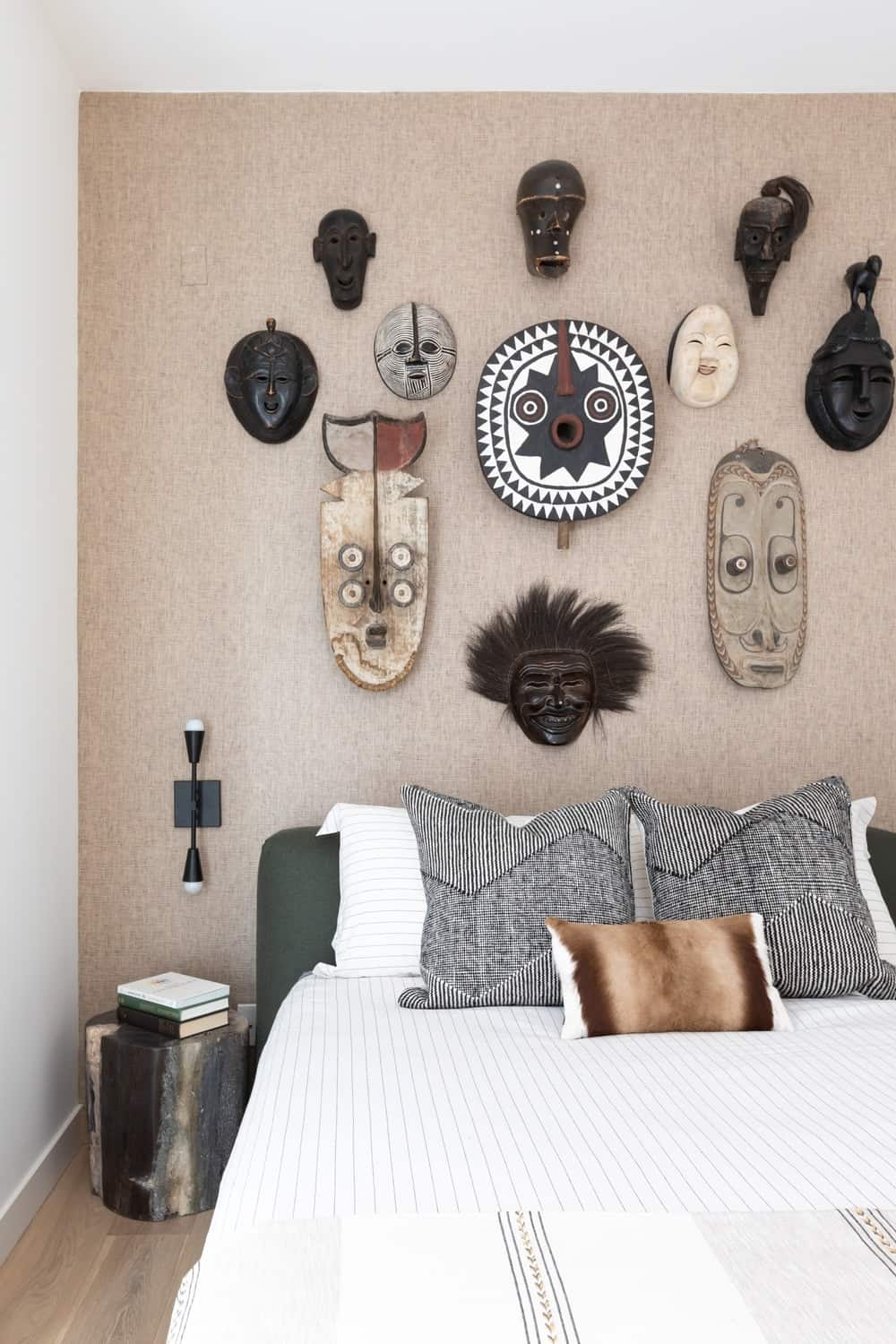 This is a closer look at the light wood wall behind the headboard of the bed. This is filled with various wall-mounted decorative tribal masks that give character to the simple tones of the bedroom.