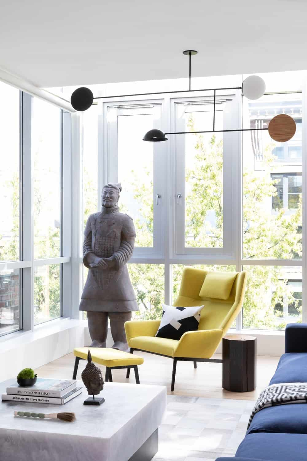 This is a closer look at the bright corner of the living room adorned with a life-size stone statue illuminated by the surrounding glass walls and ceiling. This also makes the modern lighting stand out along with the yellow armchair with a matching footstool.
