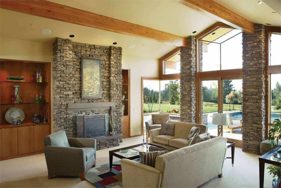 The gorgeous beige cathedral ceiling of this living room is paired with exposed wooden beams and a large glass wall that brings in an abundance of natural lighting to the light gray sofa set across from the stone structure of the fireplace that matches well with the stone pillars of the glass wall.