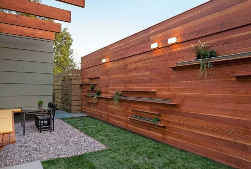 Petite backyard features modern horizontal wooden fence panels with floating shelves for plants and an L-shaped grass lawn.