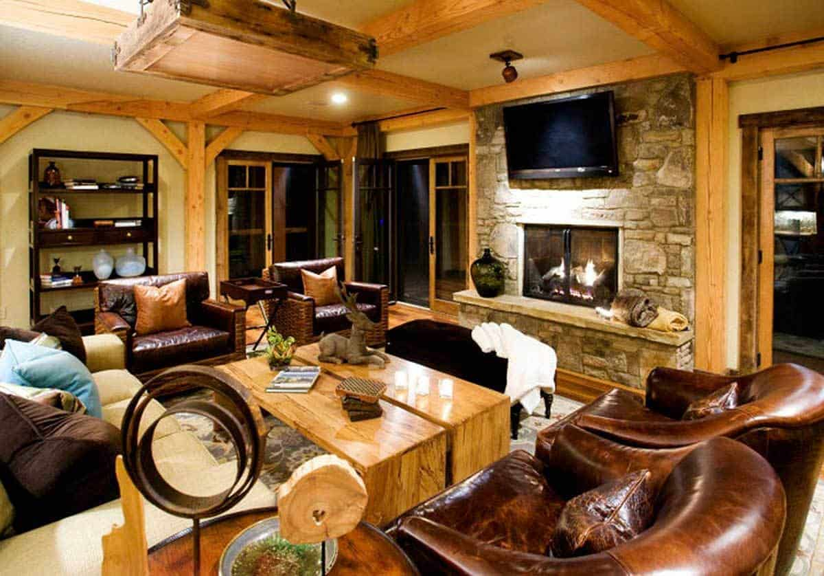 The wooden beam accents of the ceiling and walls in this living room matches well with the pair of wooden coffee tables surrounded by a sofa and two pairs of upholstered arm chairs. These are then complemented by the charming stone fireplace topped with a wall-mounted TV.