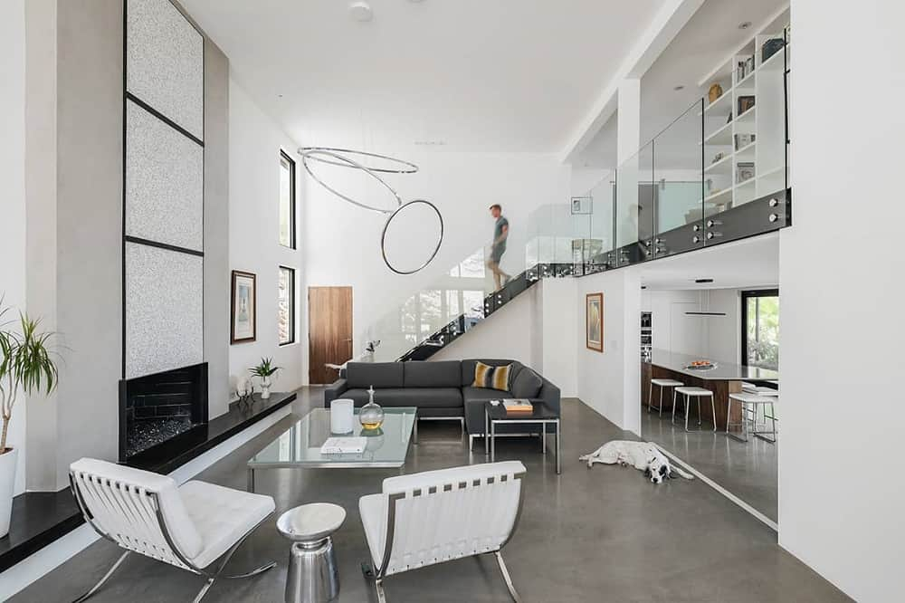 This is a full view of the modern living room that has a large white wall that houses the fireplace across from the black L-shaped sofa and the white cushioned chairs paired with a glass-top coffee table.
