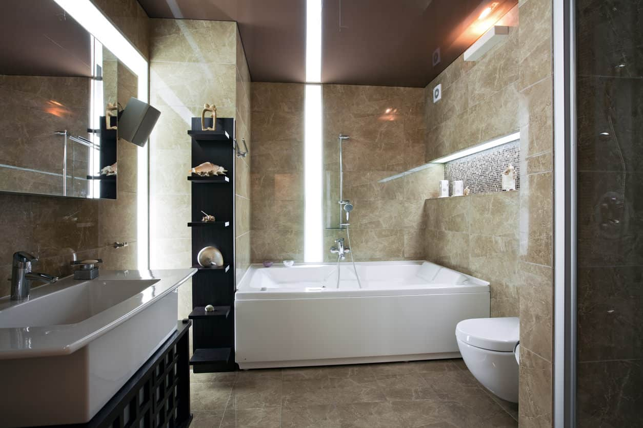Here's a masculine bathroom design with a large white trough sink perpendicular to the alcove white tub. There's a recesssed shelf above the tub for shampoo, soap and other products. A stand-out design feature here is the lighting.