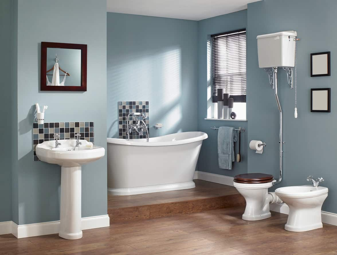 Blue primary bathroom with a modern solid-base freestanding tub in an alcove off the main bathroom space.
