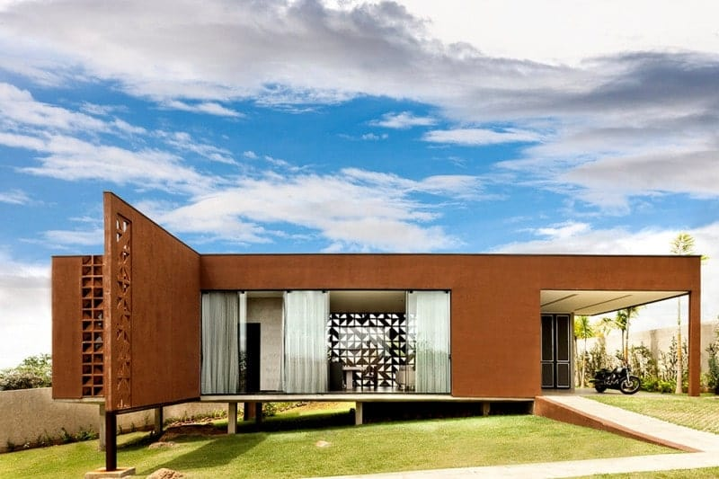 Contemporary terracotta house on a downhill slope featuring solid and glass walls. It has a green lawn and is surrounded by concrete privacy fence walls.