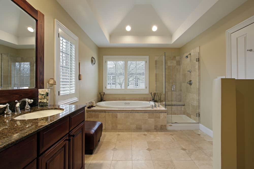 The side-by-side design of this corner bathtub and shower helps maximize the amount of space without having to have a two-in-one shower and tub combination. The dark wood on the cabinets — along with the dark marble — adds a striking touch to the lighter tiles.