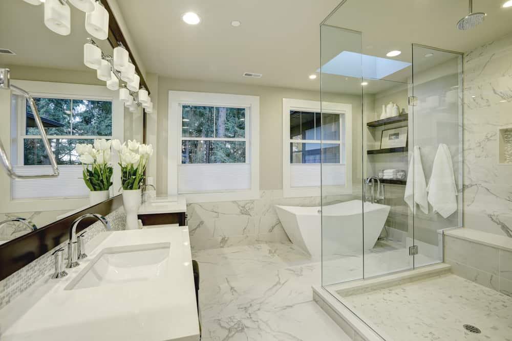 The corner bathtub in this marble-and-glass adorned bathroom is definitely a more modern, minimalist take on tubs, but it fits in with the bright design.