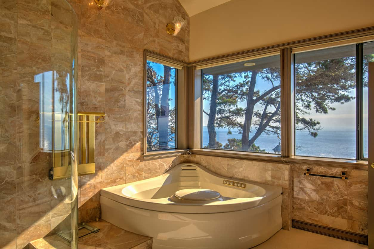 What's better than a corner bathtub? A corner bathtub with a gorgeous view of the coastline. The marble walls and gold fixtures add to the beauty in this one-of-a-kind space.