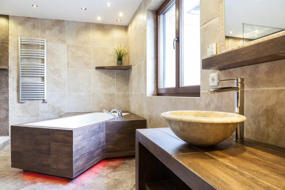 The under light adds an eye-catching touch to this unique corner bathtub design. The wood-panel siding is also pretty unique for a tub.