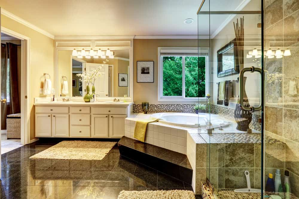 The jack-and-jill sinks and the all-glass shower flank the striking corner bathtub on each side. Bonus: The window above the tub gives an extra view while soaking in the bath.