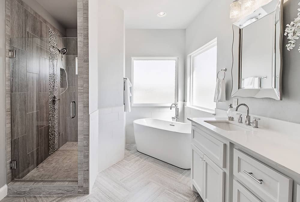 This corner bathtub style is perfect for tight spaces, like in this monochrome bathroom that features plenty of modern fixtures in white and gray colors.
