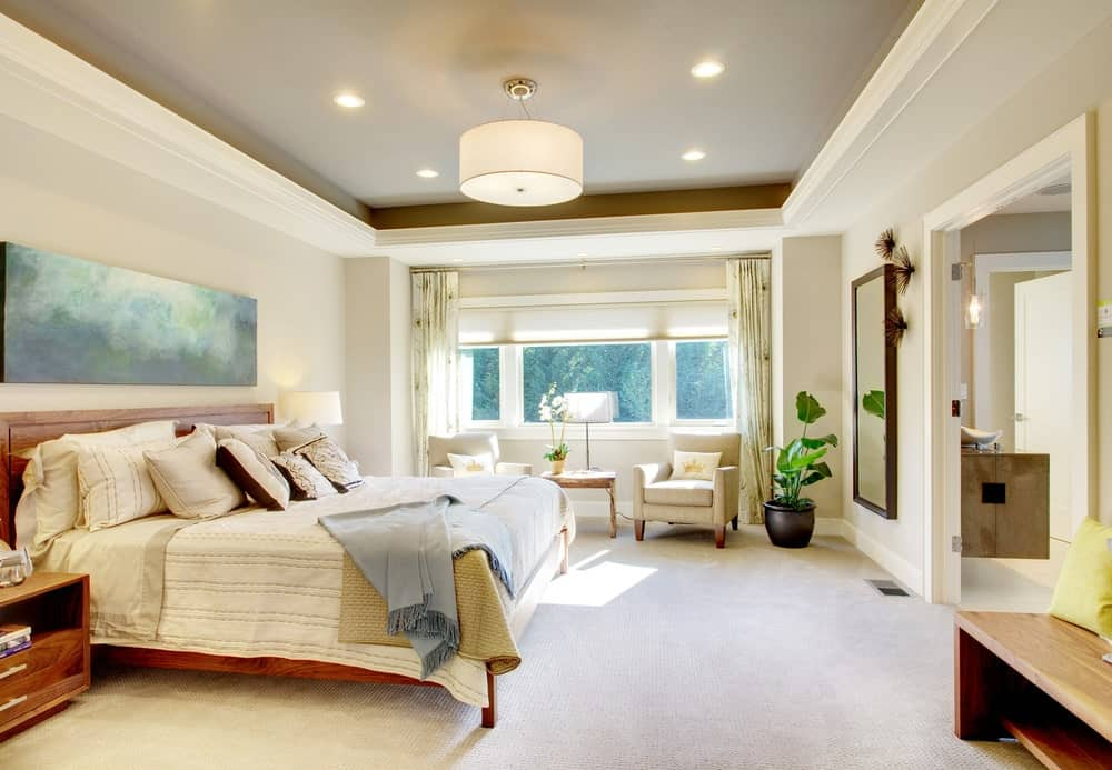 White primary bedroom lighted by a drum chandelier that hung from a tray ceiling. It features a wooden bed and carpet flooring.