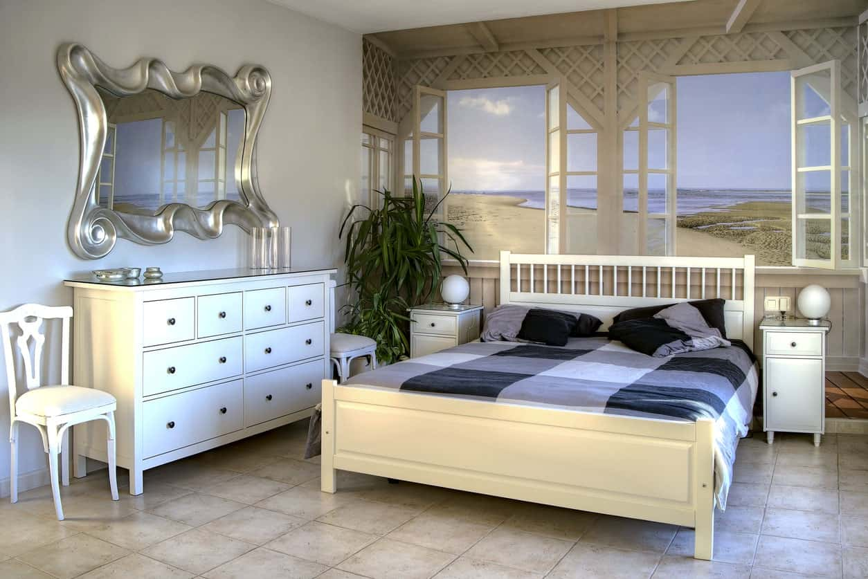 White bed with a background of the mesmerizing beach matches the white vanity paired with a silver wave wall mirror in this airy primary bedroom.
