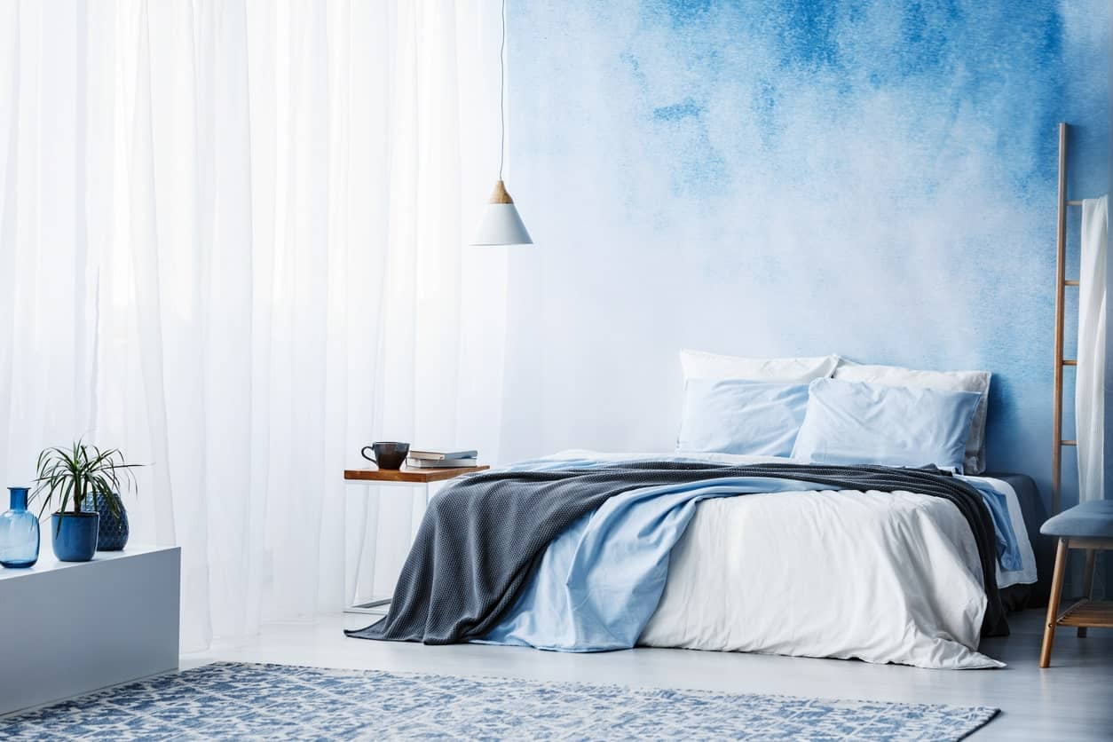 Calming primary bedroom with a bed fixed on a lovely blue wall. It has a white sheer curtain and a blue vintage rug.