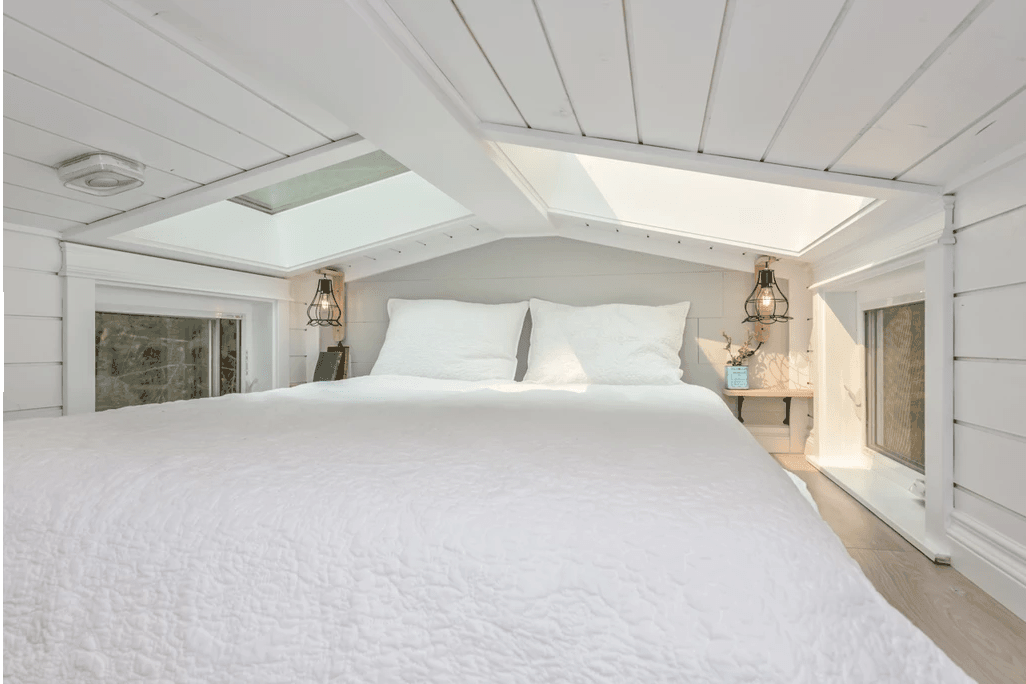 Cozy loft bedroom in tiny home with nightstands and two skylights