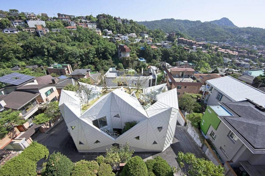 A bird's eye view of the house where you can see the surrounding neighbors and mountain. There's also a rooftop garden integrated to the house.