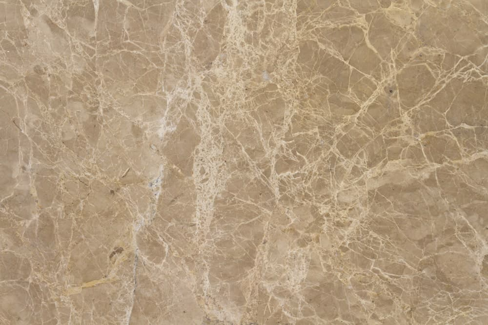Light Emperador slab with a beige background and intricate veining