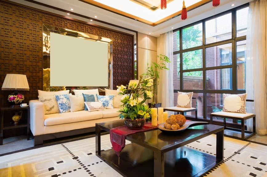 The wall behind the white cushioned sofa has oriental patterns adorned with a gold framed blank canvas that matches with the large patterned area rug under the large black wooden coffee table bearing decors and a potted plant.
