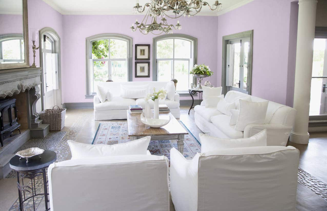 Bright living room featuring light purple walls and white seats, along with a fireplace.