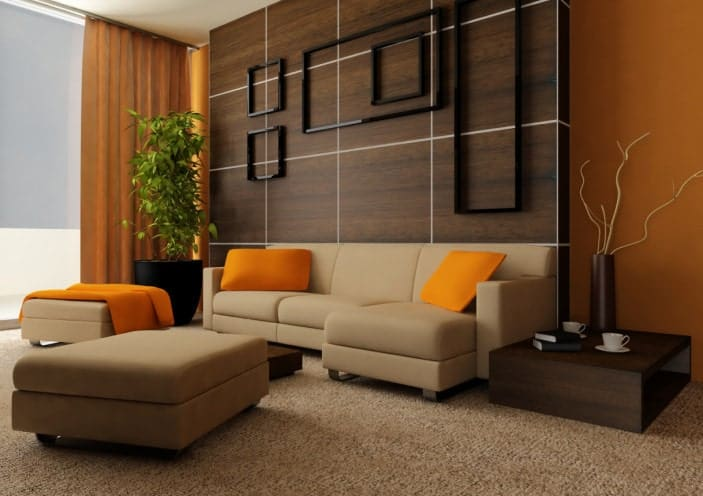 The brown carpeted flooring is complemented by the dark brown side table and the brown sectional sofa that is given a nice background wall made of dark wooden panels accented with black empty frames. This is well contrasted by the orange elements on the walls, pillows and curtain.