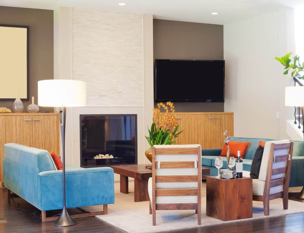 A modern glass-enclosed fireplace is embedded into a white textured wall that is flanked by two wooden cabinets that complements the dark hardwood flooring. This is contrasted by the white area rug and its blue velvet sofas flanking a wooden coffee table.