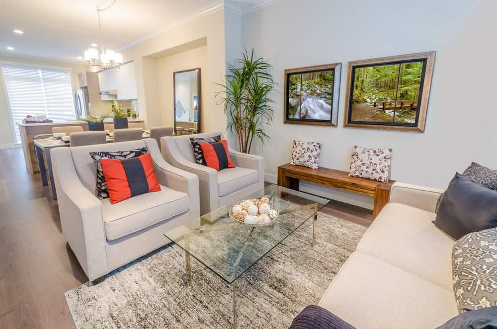The light gray walls are accented with a couple of framed photographs of a stream in a jungle. This gives a nice dash of color to the light gray sofa and cushioned armchairs flanking the glass-top coffee table over an industrial gray area rug.