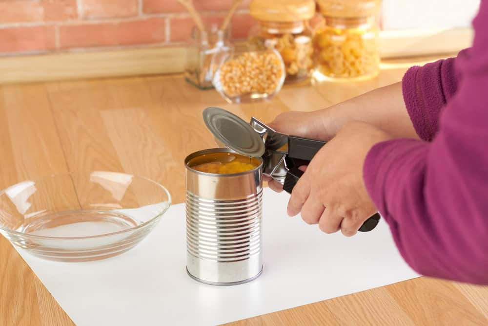 Opening a canned food using a manual can opener.