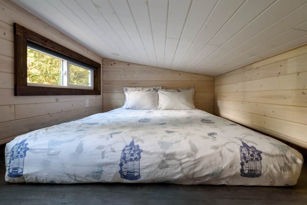 Minimalist tiny house bedroom loft with shed style ceiling